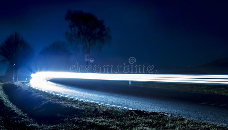Car driving on road at night stock photography