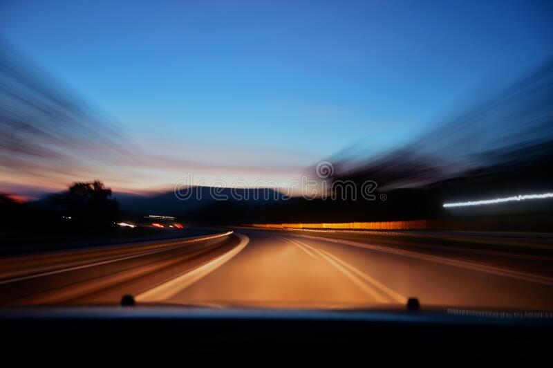 Car driving on road at sunset stock images