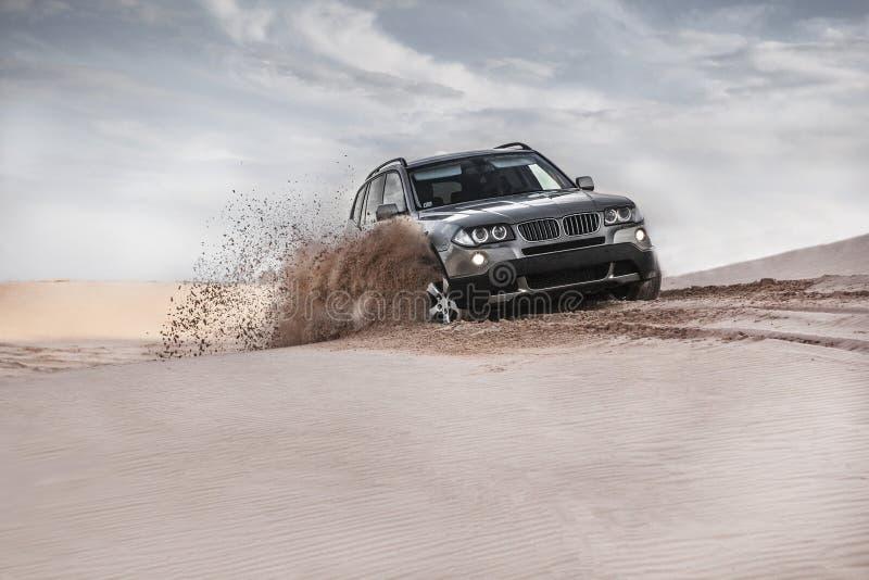 Car driving through sand dune stock photos