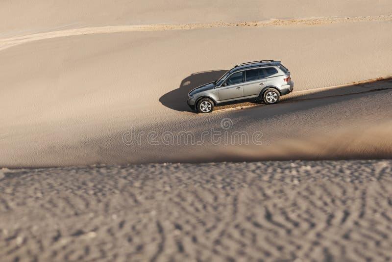 Car driving through sand dune stock image