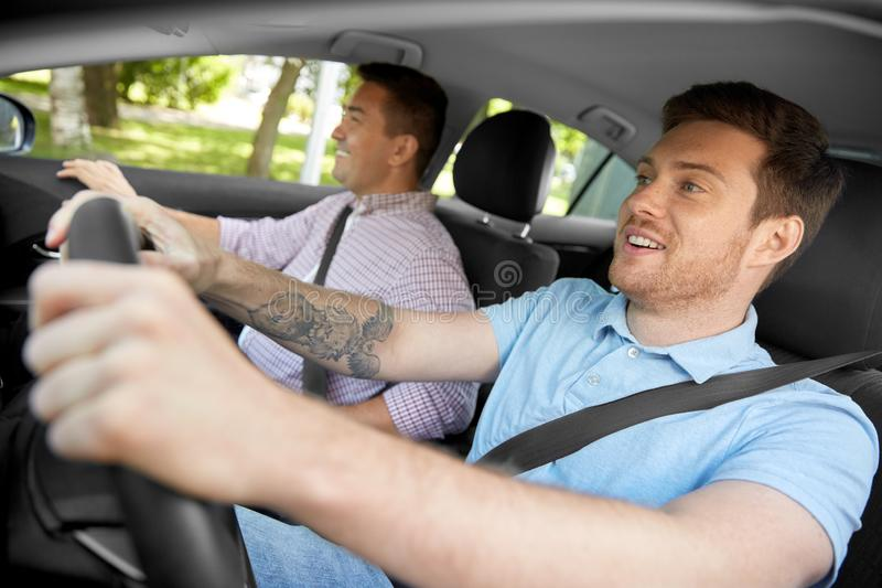 Car driving school instructor and male driver. Car driving lesson and carpooling concept - instructor on passenger seat and young driver laughing stock photo