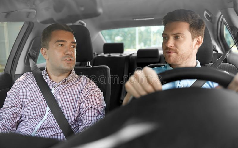 Car driving school instructor and male driver. Car driving lesson and carpooling concept - instructor on passenger seat and young driver talking stock image