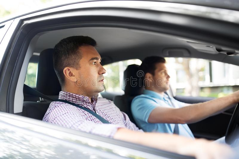 Car driving school instructor and male driver. Car driving lesson and carpooling concept - instructor on passenger seat and young driver royalty free stock images