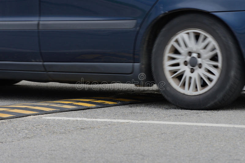 Car driving through a speed bump close-up stock image