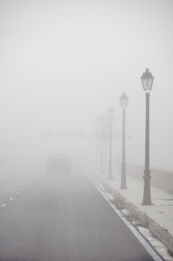 Car driving vanish into the fog. Car driving vanish into the morning fog royalty free stock photo