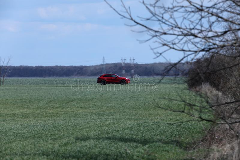 Car driving in the wild. Car driving a road in the middle of a green field stock photography