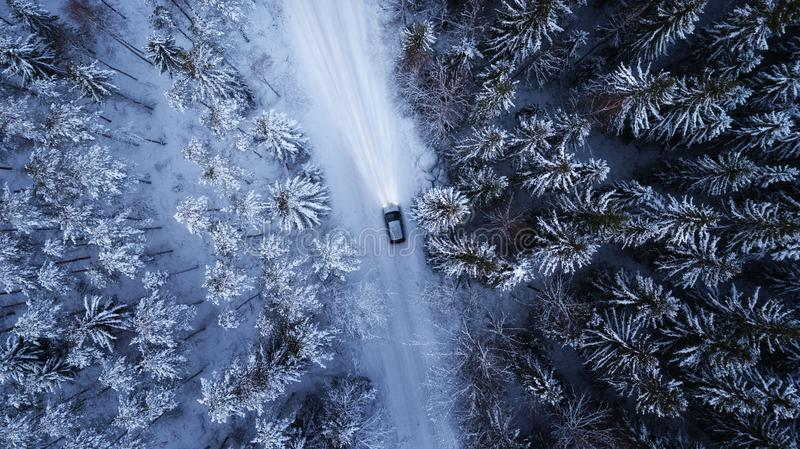 Car driving through the winter snowy forest on country road at night. Top down view. stock photo