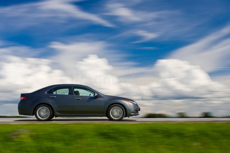 Car drivng fast. Blue sky and meadow royalty free stock photography
