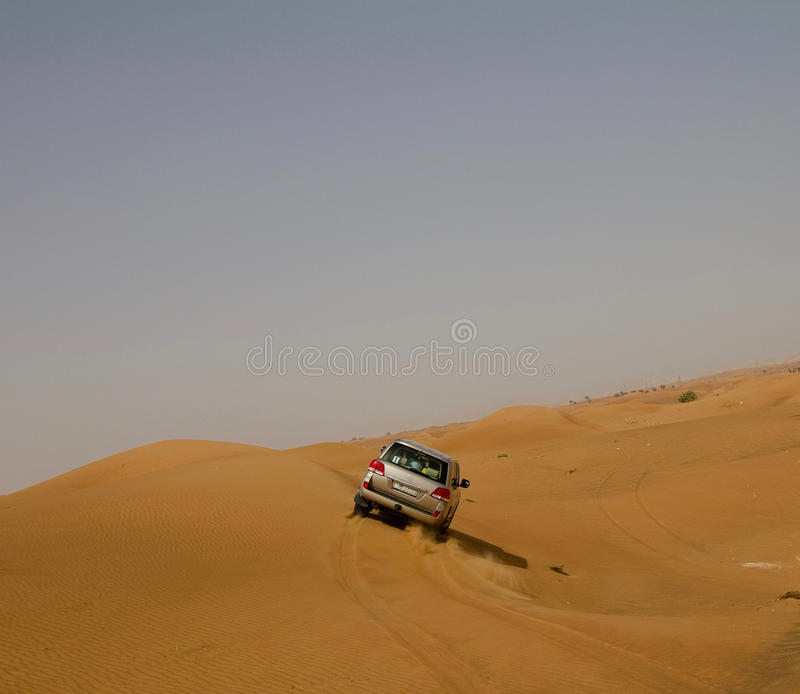 A car dune bashing in a desert in Dubai, UAE. A car SUV dune bashing in a desert in Dubai, UAE stock photo