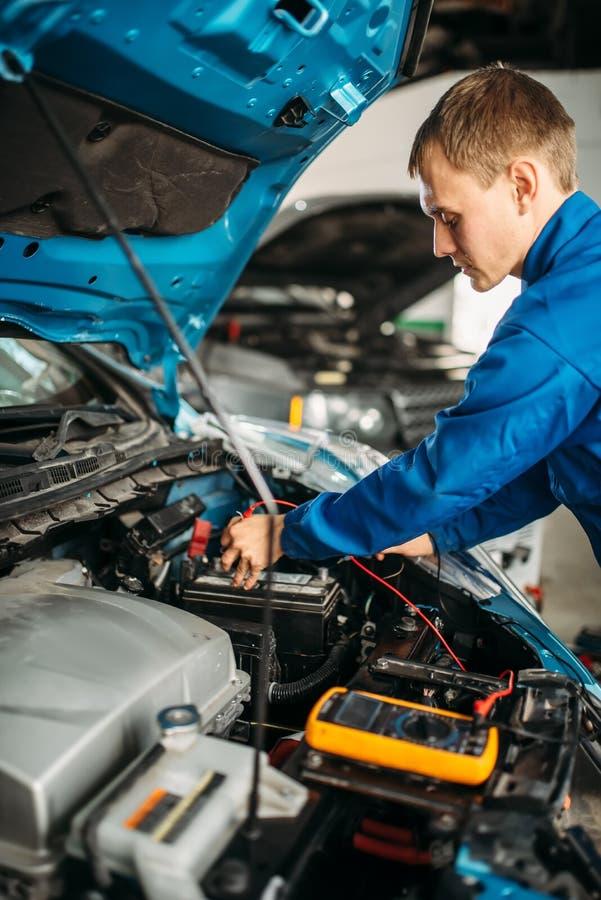Car electrician checks the battery level royalty free stock photos