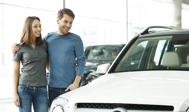 This car is exactly what we want. Beautiful young couple standing at the car dealership and making their decision royalty free stock image