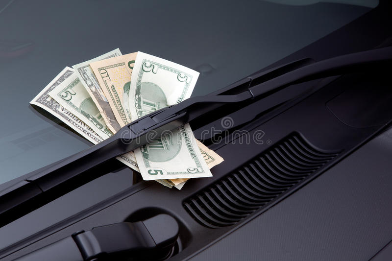Car expenses. Symbolized by dollars on a windscreen wiper stock images