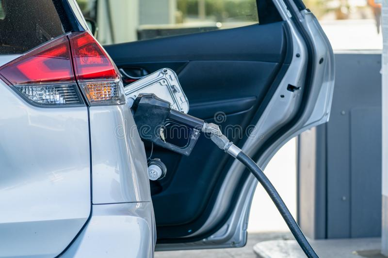 Car filling up gas tank at a gas station, with the door open stock image