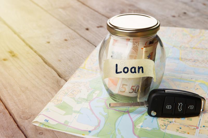 Car finance concept - money glass with word Loan, car key. And roadmap royalty free stock images