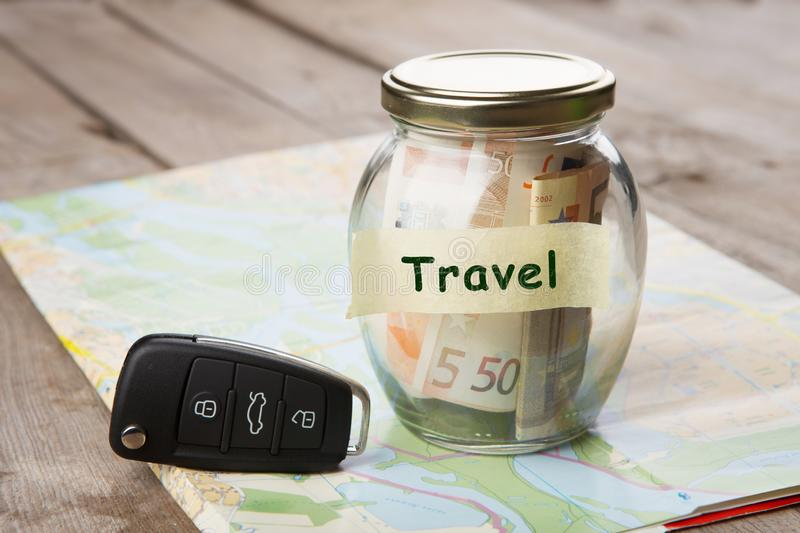 Car finance concept - money glass with word Travel, car key and roadmap. Rent, auto, rental, sale, security, driving, insure, buy, alarm, vehicle, service stock photos