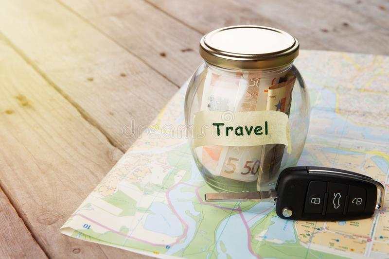 Car finance concept - money glass with word Travel, car key and roadmap. Rent, auto, rental, sale, security, driving, insure, buy, alarm, vehicle, service stock photography