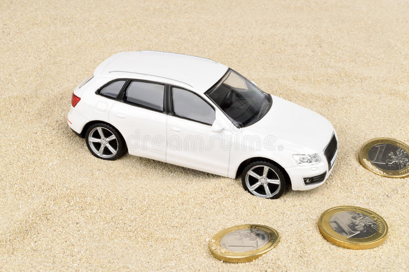 Car Finance Desert. A financial metaphor on Euro car finance. A car stranded in the desert with Euro coins royalty free stock photo