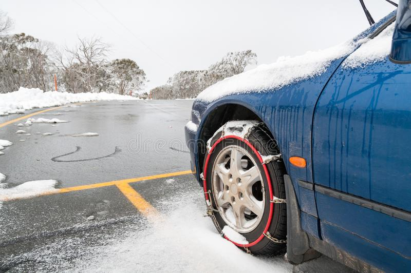 Car with fitted tire chains or snow chains on its front wheels stock photo