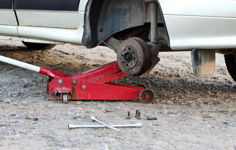 Car fixed in the garage, Hydraulic floor jack lift a car, Wheel without tire, Key cross road and four nuts stock image