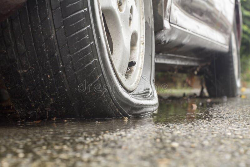 Car flat tire in rainy day. Car flat tire onstreet in rainy day stock photo