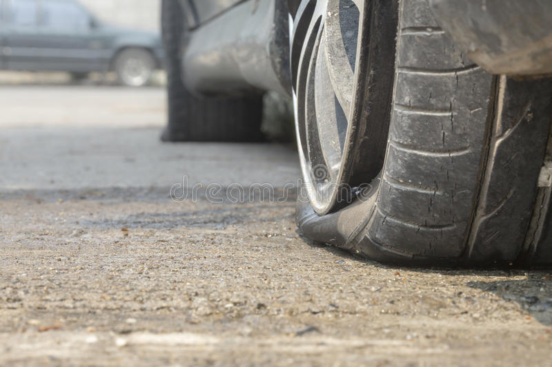 Car flat tire on road. Car flat tire on concrete road royalty free stock photo