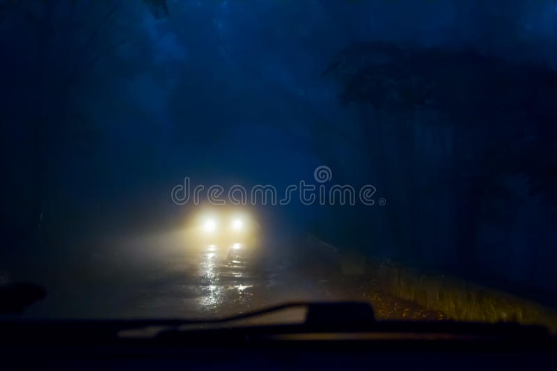 Car in the fog. Oncoming cars in the fog on a mountain road. Poor visibility stock photo