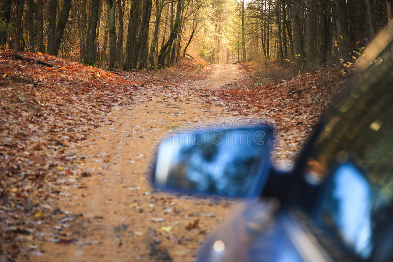 The car on forest road in the fall. The car on the road, a visible image in the mirror, forest road in the fall royalty free stock image