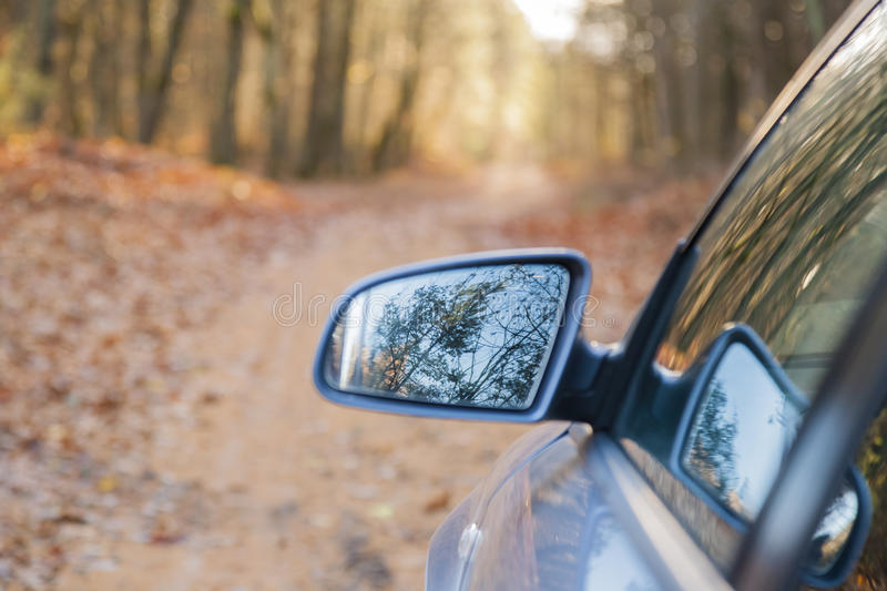 The car on forest road in the fall. The car on the road, a visible image in the mirror, forest road in the fall royalty free stock photos