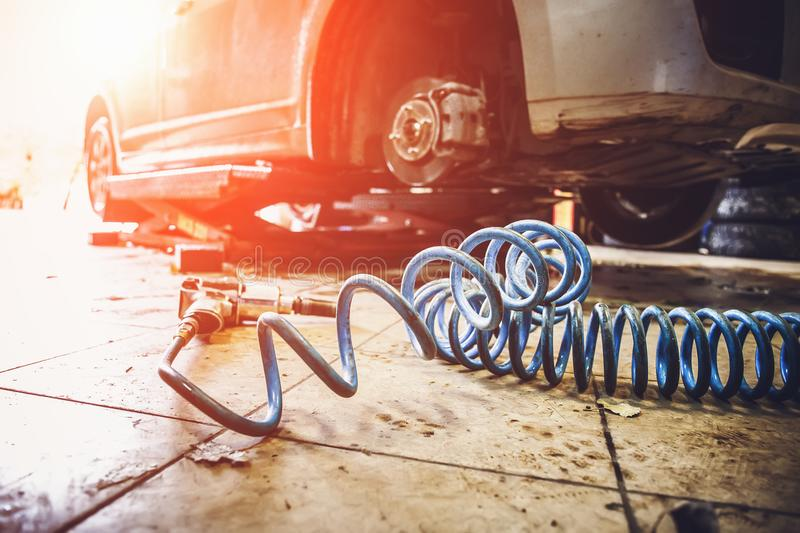 Car in garage in auto mechanic repair service work shop with special machine repairing equipment. Sunlight effect, toned royalty free stock image
