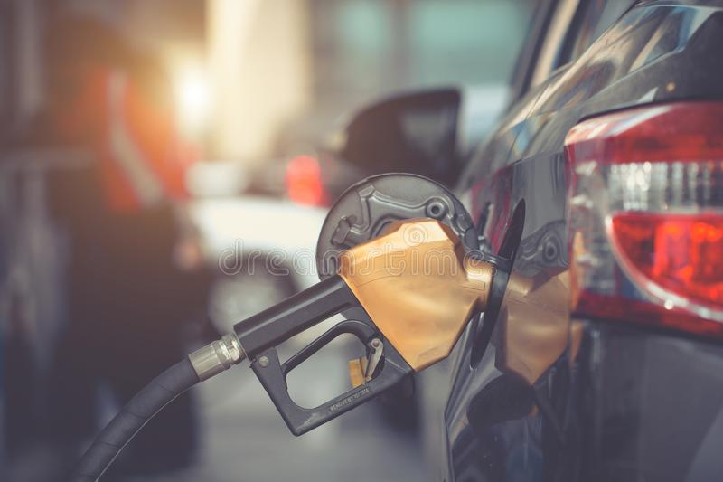Car gas nozzle refuel fill up with petrol gasoline at a gas station. Close up. .Gas pump nozzle in the fuel tank of bronze car, stock photos