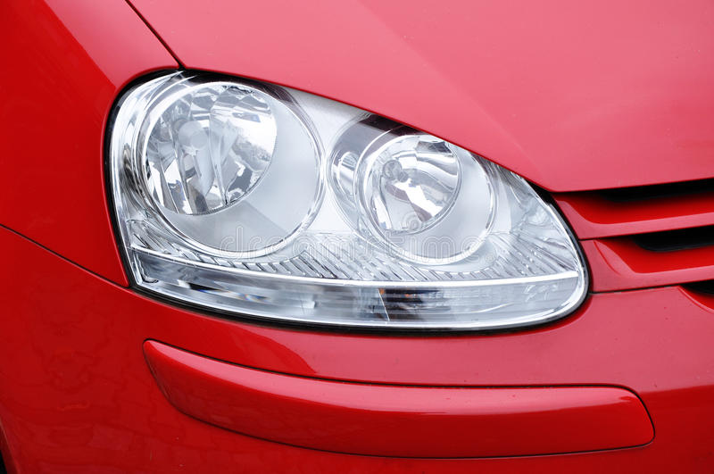 Car headlamp red. Red car, close-up of headlamp, industry stock images