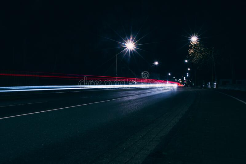 Car headlights approaching at night stock photo