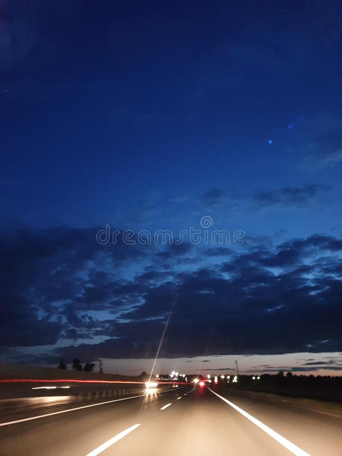 car headlights illuminate the night highway, dangerous night-time driving royalty free stock photo