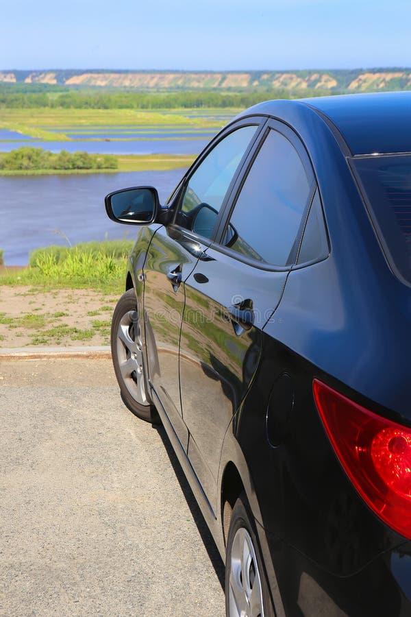 Car at high river bank. Dark blue car at high river bank royalty free stock image