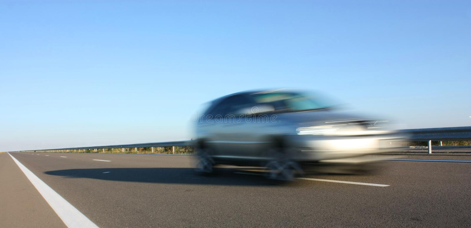 A car on a highway. A fast car on a highway movement stock image