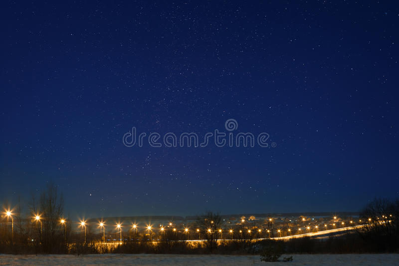 Car highway with star sky, lit by lanterns. Night landscape in t royalty free stock image