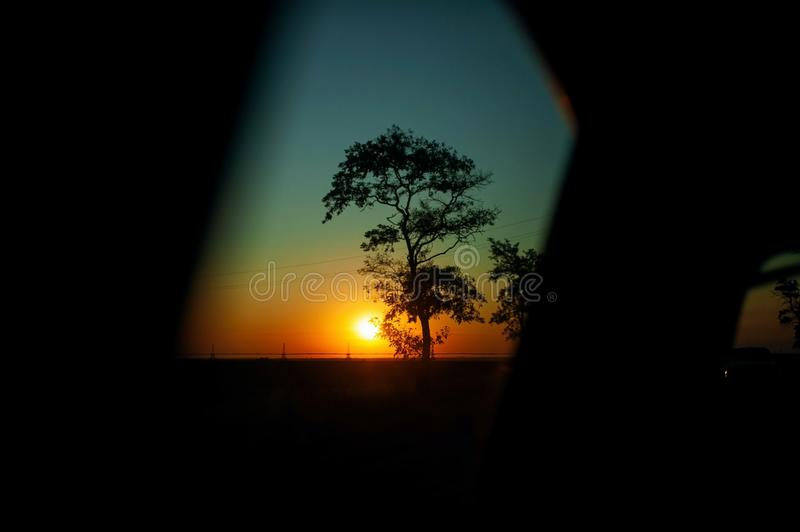 Car on highway. sunset in car mirror reflection. road trip at night. stock images