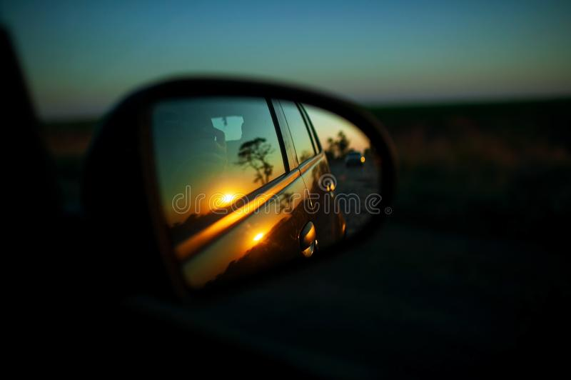 Car on highway. sunset in car mirror reflection. road trip at night. stock photography
