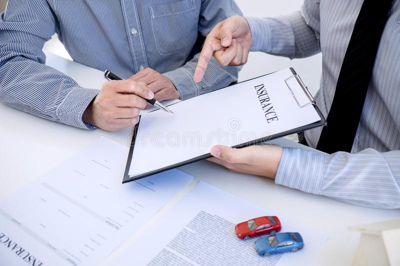 Car and Home insurance concept, broker agent presenting and cons. Ult to customer to decision making sign insurance form agreement, home and car model stock image