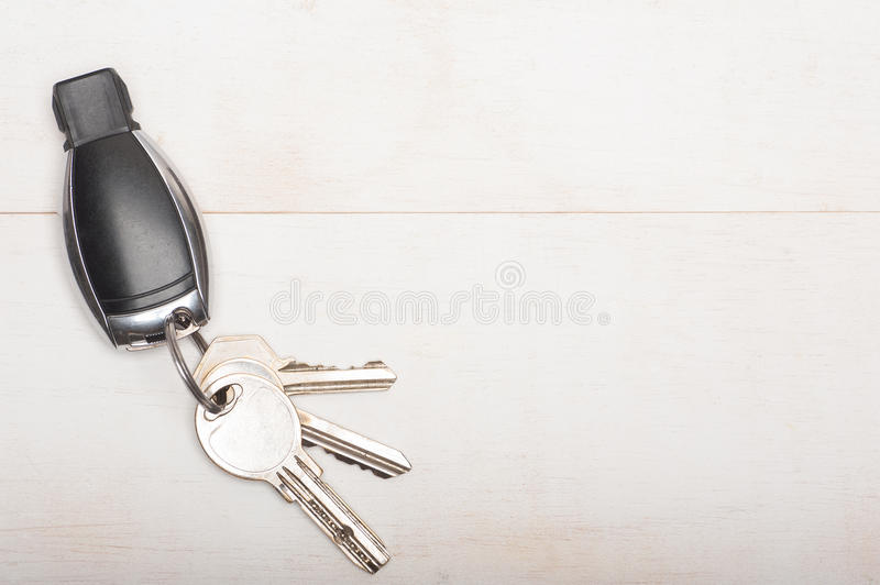 Car and home keys. Close up of car and home keys on white wooden background with copy space royalty free stock photography