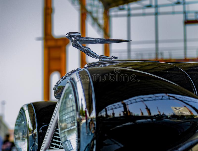 Car hood and statuette of an old Cadillac at the American car ex. Detail of the car hood, the statuette and the front lights of a vintage Cadillac in an stock image
