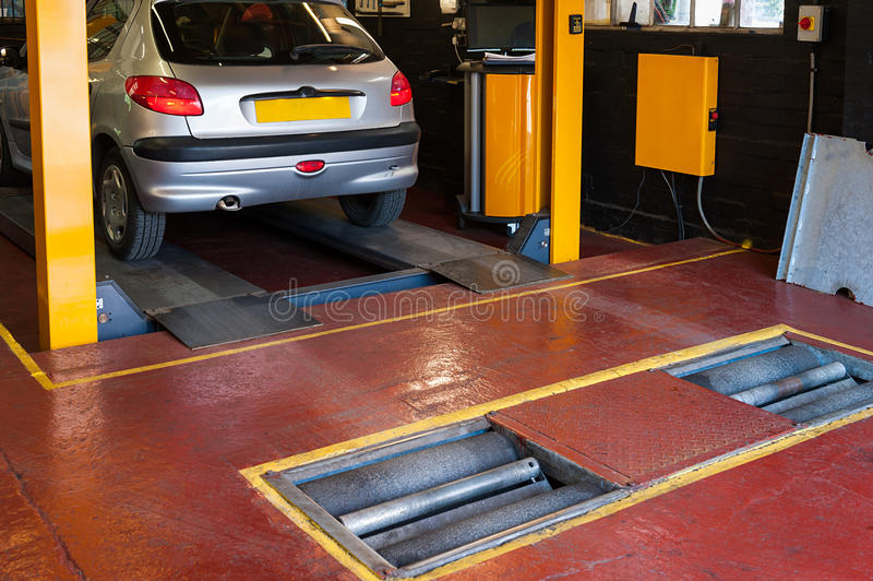 Car inspection. In automotive service garage with a car brake checking machine royalty free stock photography