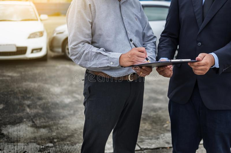 Car insurance agent send a pen to his customers sign the insurance form on clipboard while examining car after accident claim.  royalty free stock images