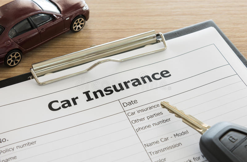 Car insurance. Application form with car model and key remote on desk royalty free stock photos