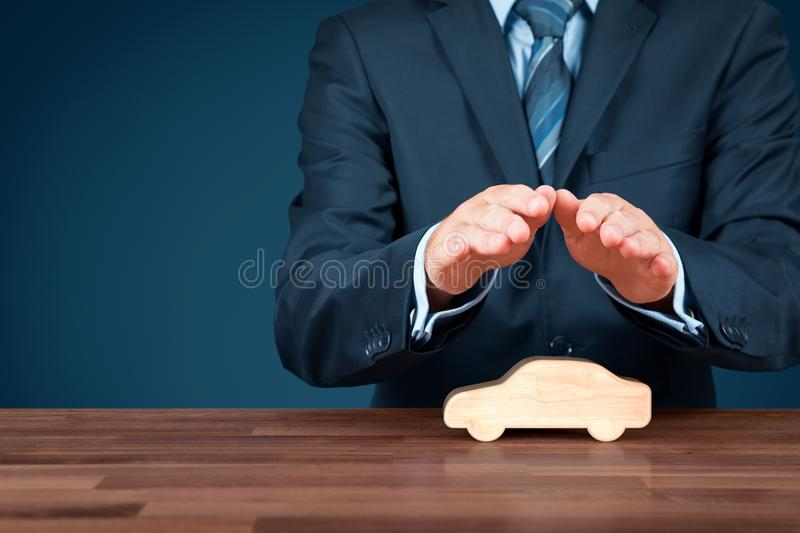 Car insurance. Car automobile insurance and collision damage waiver concepts. Insurer insurance agent with protective gesture and wooden model of a car royalty free stock photo