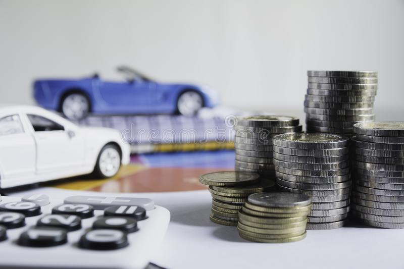 Car insurance and car service with stack of coins. Toy car for accounting and financial concept.  royalty free stock image