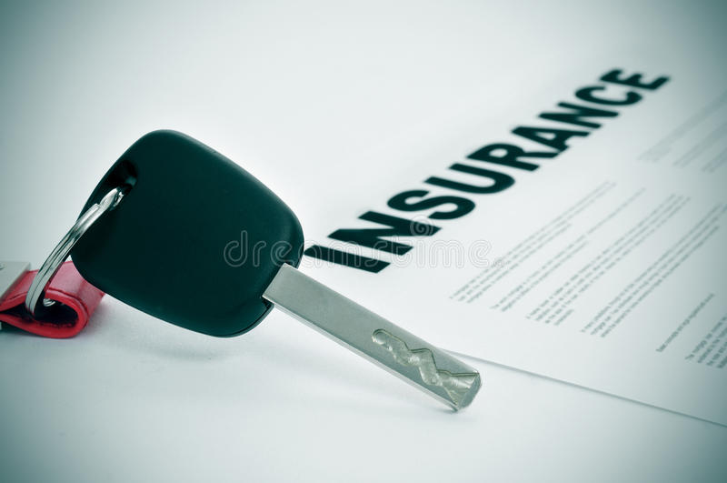 Car insurance. Closeup of a car key and a insurance policy on a white surface royalty free stock photography