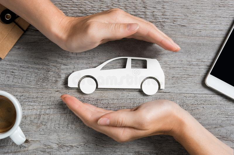 Car insurance concept. Hands protecting icon of car over wooden table. Top view of hands showing gesture of protecting car. Car insurance and automotive business stock photography