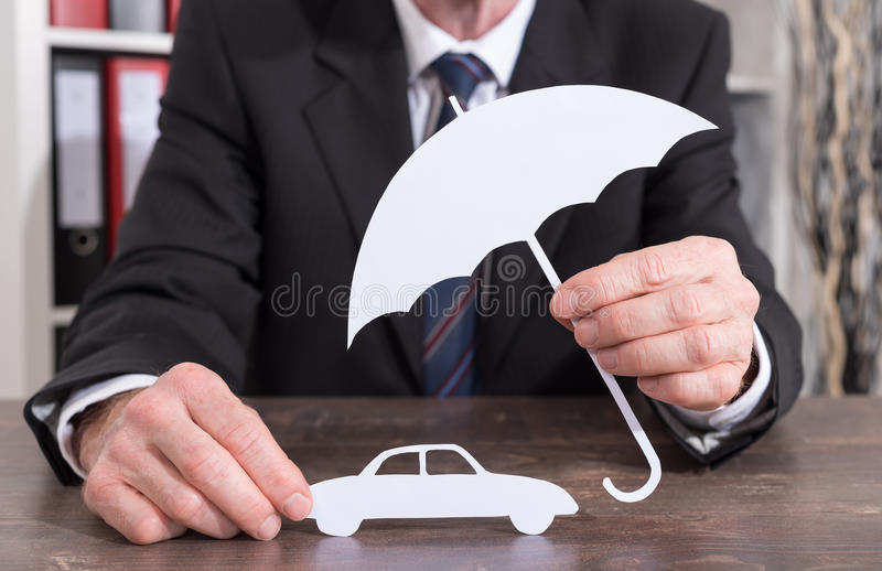 Car insurance concept. Car protected with an umbrella by an insurer - insurance concept stock images