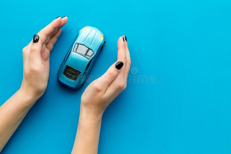 Car insurance concept. Safety of auto. Car toy in female hands on blue background top view copy space. Car insurance concept. Safety of auto. Car toy in female royalty free stock images